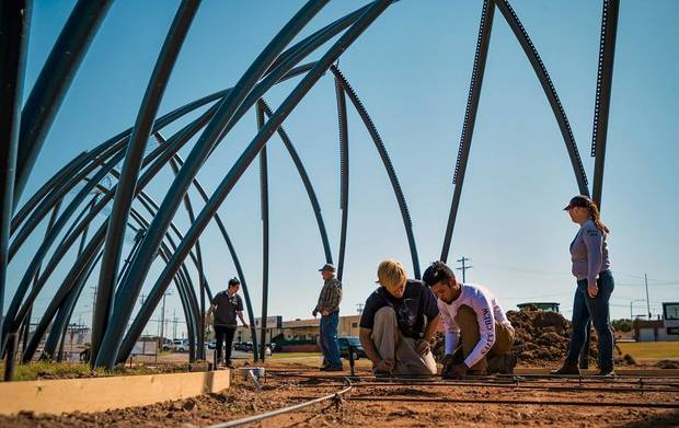 "Participants in the CDSA YouthBuild program work on the pathway for artist Romy Owens' large-scale public art project ""Under Her Wing Was the Universe"" in Enid, Okla. on Thursday, Oct. 17, 2019. Devised as a pavilion that can be used for picnics, parties and other intimate events, Owens said the large-scale public art project will feature a sculptural cover with a starry light installation underneath, giving the sense of stepping under a large bird´s wing and discovering a universe under it. [Chris Landsberger/The Oklahoman]"