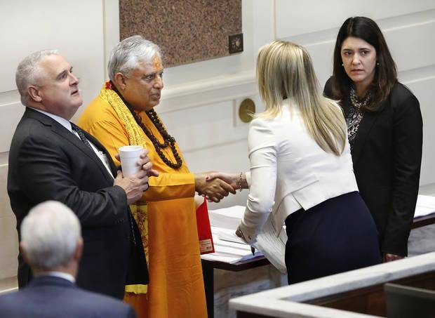 Hindu statesman Rajan Zed greets senators on the floor of the Oklahoma Senate after he delivered the invocation for the legislative body on Monday at the State Capitol. He is shown shaking the hand of Sen. A. J. Griffin. At left is Sen. Mike Schulz, president of the Senate, and at right is Sen. Stephanie Bice, assistant floor leader and the legislator who sponsored Zed's stint as chaplain for the day. [Photo by Jim Beckel, The Oklahoman]