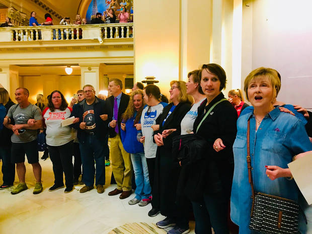 "People link arms and form a circle around the fourth floor rotunda to sing ""This Little Light of Mine"" at the conclusion of a prayer gathering on Thursday at the State Capitol. [Photo by Carla Hinton, The Oklahoman]"