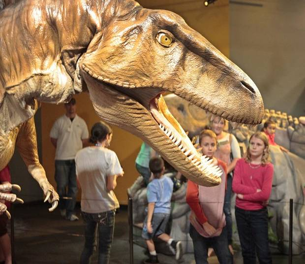 "Visitors get a look at a Acrocanthosaurus in the exhibit ""Red Dirt Dinos"" at Science Museum Oklahoma, Thursday, October 10, 2013. The popular exhibit has returned to the Oklahoma City museum. [The Oklahoman Archives photo]"