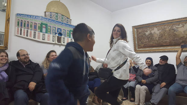 A young Palestinian boy dances with Kathy Dodd of Tulsa after a meal of Maklouba during the Oklahoma Religions United group's trip to Israel and the Palestinian Territories. [Photo by Carla Hinton, The Oklahoman]