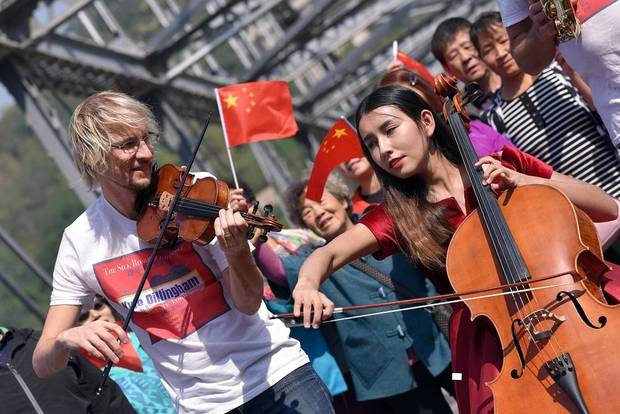 Oklahoma fiddler Kyle Dillingham performs an impromptu jam with Chinese cellist on Zhongshan Bridge. [Photo by Yunfan Photography]