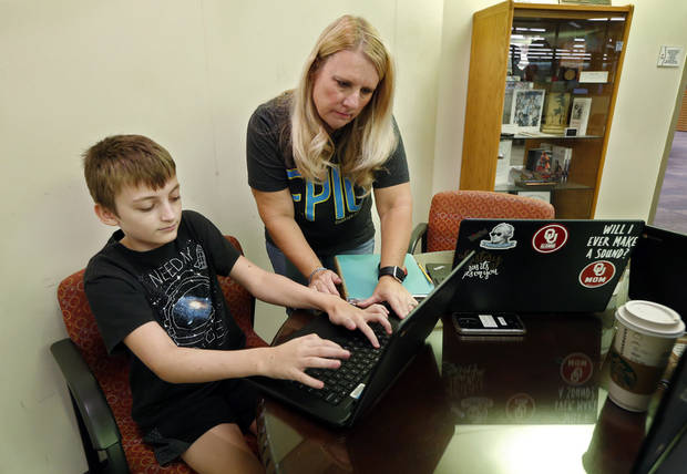 EPIC Charter School teacher Regina Bell helps student Eli Real, 11, of Norman, as Bell met with students in September at Norman Public Library Central. [OKLAHOMAN ARCHIVES/STEVE SISNEY]