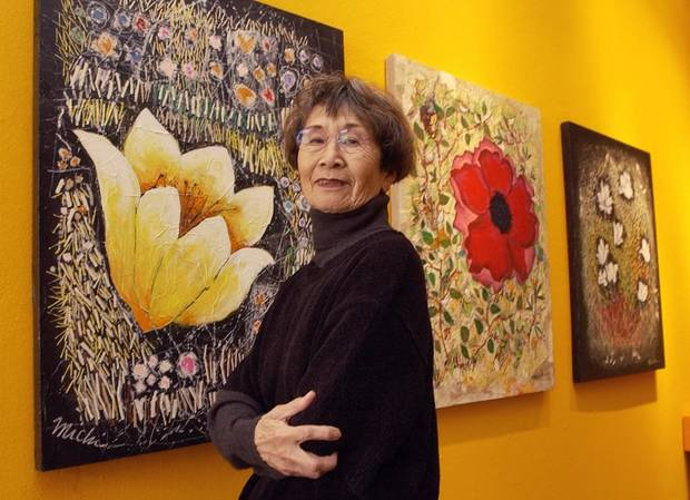 "Artist Michi Susan poses with mixed-media paintings in her ""Wildflowers"" series in 2004 at JRB Art at the Elms in the Paseo Arts District. [The Oklahoman Archives]"