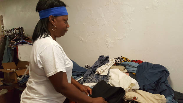 Volunteer Janet Sanders, a VA Medical Center employee, straightens clothing during a clothes giveaway held as part of the Helping Hands 10th anniversary celebration on Aug. 27 at The Christ Experience, 1006 NE 17. [Photo by Carla Hinton, The Oklahoman]