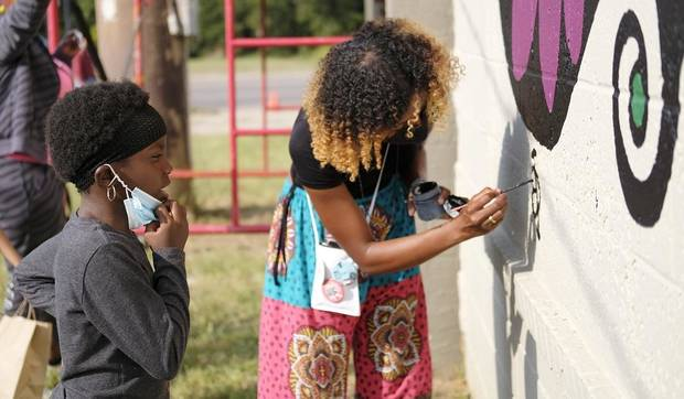 "Oklahoma artist Ebony Inman Dallas, right, works on a mural for ""Celebration of With Love,"" an Eastside Public Art Project where six local Black artists painted murals on the side of The Market building at 1708 NE 23. The event, which included music and food, was on Saturday, October 3, 2020. [Doug Hoke/The Oklahoman Archives]"