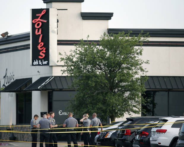 FILE - In this May 24, 2018, file photo, police officers stand outside Louie's On The Lake restaurant in Oklahoma City after a man shot and wounded several patrons inside the restaurant. Police recovered 9 millimeter ammunition, notebook writings, a computer, a laptop and cellphones from the apartment of Alexander Tilghman in a warrant issued hours after the shooting and filed Tuesday, May 29. Tilghman was fatally shot by two civilians. (Sarah Phipps/The Oklahoman via AP, File)