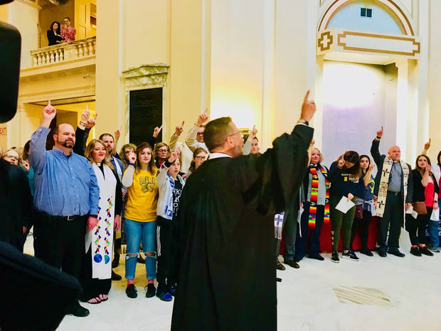 "The Rev. Mitch Randall encourages the crowd to hold up their index finger to represent their plan to use their their ""little light"" or voice to support public education at the conclusion of a prayer gathering on Thursday at the State Capitol. [Photo by Carla Hinton, The Oklahoman]"