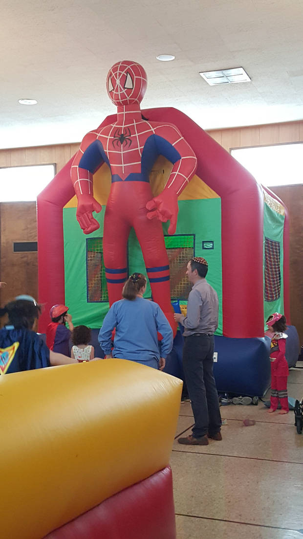 "A Spider-man bounce house was among the inflatables and other youth-oriented activities offered at Emanuel Synagogue's recent Purim festivities in Oklahoma City. Theme for the Purim party was ""Heroes and Villains."""