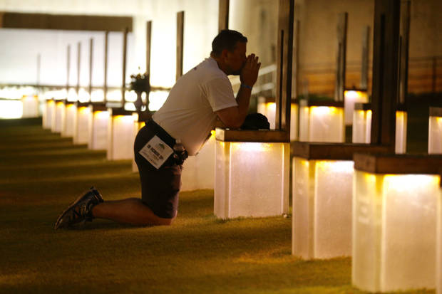 Kyle Genzer prays at the chair of his mom Jamie fialkowski Genzer before the 20th Anniversary Remembrance Ceremony, Sunday, April 19, 2015, at the Oklahoma City National Memorial and Museum in Oklahoma City.
