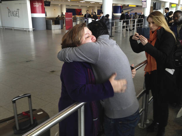A woman is embraced Sunday by her son-in-law at John F. Kennedy International Airport in New York. The son-in-law said that the woman had traveled from Iran and had been detained after arriving. President Donald Trump's executive order Friday suspended all immigration and visa processes for nationals from a handful of countries with terrorism concerns, including Iran, for 90 days. (AP Photo/Seth Wenig)