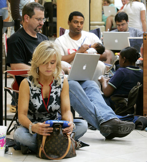 From front to back, Vicki Baldini, Darrell Solomon, Ronald Henderson, holding his 8-week-old son, Ronald Henderson Jr., next to his wife, Jamila Henderson, and others wait in line to buy the iPhone at the Apple Store in Penn Square Mall in Oklahoma City, Friday, June 29, 2007. The line outside Penn Square Mall began forming at 3:30 a.m.[THE OKLAHOMAN ARCHIVES]