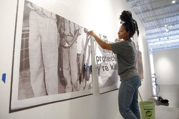 "Artist Tatyana Fazlalizadeh installs her artwork for her exhibit ""Oklahoma Is Black,"" a depiction and celebration of Oklahoma City's rich black history, on Feb. 19 at Oklahoma Contemporary in Oklahoma City. [Bryan Terry/The Oklahoman]"