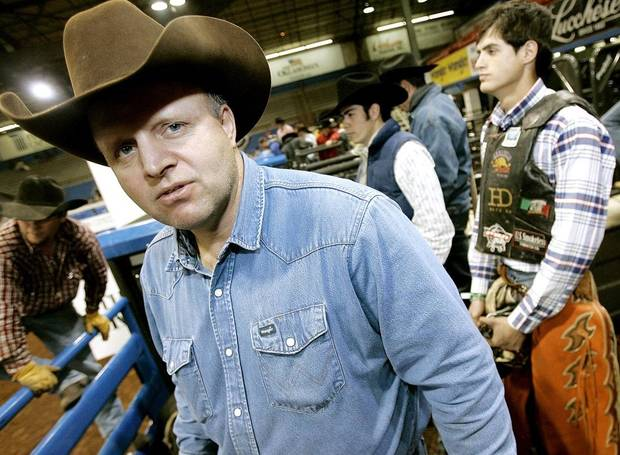 Cody Lambert (left) poses on the chute during an open competition at the PBR US Smokeless Challenger Tour Championship at the Lazy E Arena in Guthrie, Okla., on Monday, Feb. 12, 2007. [The Oklahoman Archives]