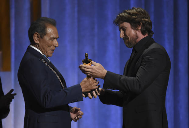 Christian Bale, right, presents an honorary Oscar to Wes Studi at the Governors Awards on Sunday, Oct. 27, 2019, at the Dolby Ballroom in Los Angeles. [Photo by Chris Pizzello/Invision/AP]