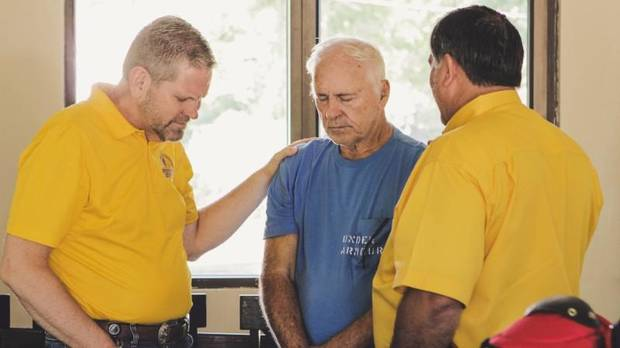 Alan Quigley, Baptist General Convention of Oklahoma mobilization team leader, prays with Oklahoma Baptist Disaster Relief Director Don Williams and a homeowner in the Houston area. [Photo by Baptist General Convention of Oklahoma]