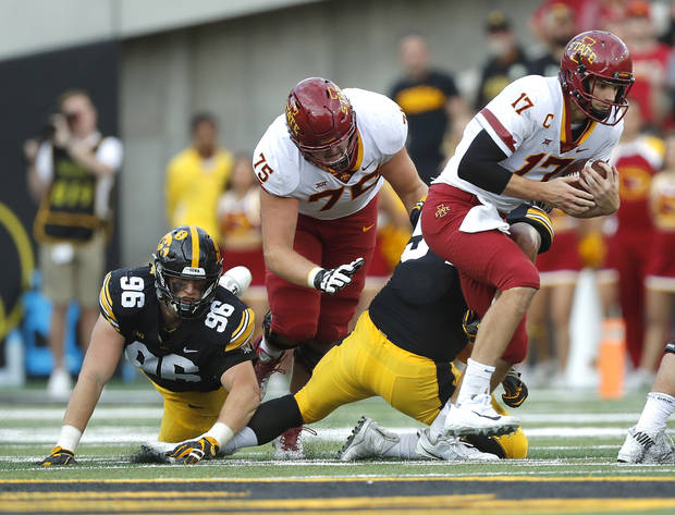 Iowa State quarterback Kyle Kempt tries to get away from an Iowa defender. (AP Photo)