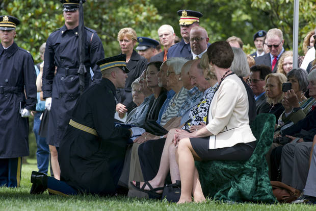 Army Capt. Lukas Findley presents the American flag to Fern Bridges, the widow of Army Air Forces Tech Sgt. Allen Chandler, 23, of Fletcher, Okla., during a group burial for five Army Air Forces crewmembers of a B-17 bomber shot down during a mission over Germany in World War II, at Arlington National Cemetery, in Arlington, Va., on June 27. [Photo by Cliff Owen, Associated Press]