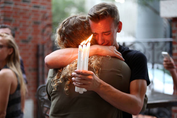FILE - In this Sunday, June 12, 2016 file photo, Brett Morian hugs an fellow mourner during a candlelight vigil for those killed at the Pulse nightclub in Orlando, Fla. The worst mass shooting in modern U.S. history unfolded on Latin Night at the gay nightclub. The gunman, Omar Mateen, killed 49 people over the course of three hours before dying in a shootout with SWAT team members. During the standoff, he pledged allegiance to the Islamic State. (Joshua Lim/Orlando Sentinel via AP)