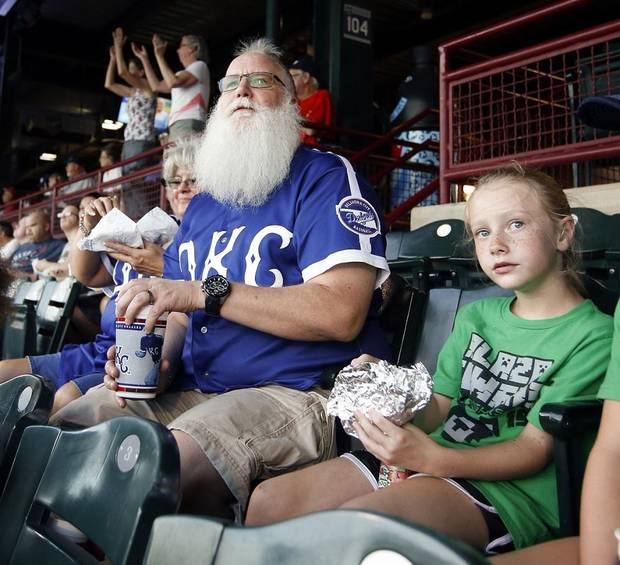 Ron Herendeen, known as Santa Ron, watches the Oklahoma City Dodgers with Tenley Richmond, 8, as he and his Team Santa kids attend a baseball game at the Chickasaw Bricktown Ballpark in Oklahoma City, Friday, Aug. 24, 2018. Team Santa is a program to promote health and fitness in youngsters that Santa Ron started after he was diagnosed with Type 2 diabetes. Photo by Nate Billings, The Oklahoman