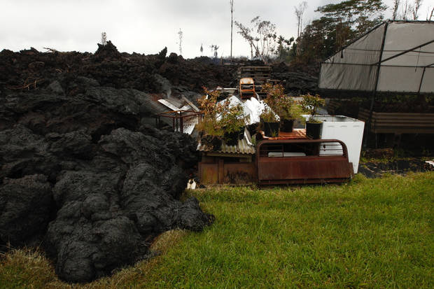 Lava continues to overrun property along Hookupu Street, Monday, May 7, 2018, in Pahoa, Hawaii. Hawaii's Kilauea volcano has destroyed homes and spewed lava hundreds of feet into the air, leaving evacuated residents unsure how long they might be displaced. (Jamm Aquino/Honolulu Star-Advertiser via AP)