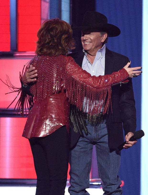 Reba McEntire, left, greets George Strait as he walks onstage to present the Dick Clark artist of the decade award at the 54th annual Academy of Country Music Awards at the MGM Grand Garden Arena on Sunday, April 7, 2019, in Las Vegas. (Photo by Chris Pizzello/Invision/AP)
