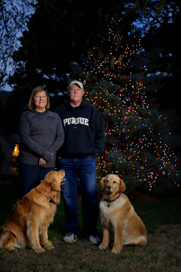 "Mark and Carol Lester, with their dog Darcy, at right, and their son's dog Sydney, left, pose for a picture in front of their ""Hope Tree"" outside their Edmond, Okla., home, Saturday, April 4, 2020. Mark Lester said he put lights on a tree in front of his house two weeks ago to cast a little brightness in gloomy times. [Bryan Terry/The Oklahoman]"