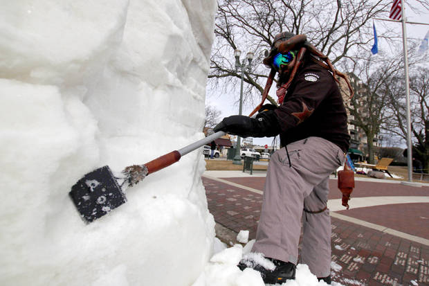 "In this Jan. 31. 2018 photo, Dusty Thune, from St. Paul, Minn., carves a snow block at the U.S. National Snow Sculpting Championship in Lake Geneva, Wis. Fifteen teams from 10 states have gathered in Wisconsin for the annual event. The Minnesota team, of which Thune is part, is creating a twisted President Donald Trump face in a suit called ""Peep,"" with the caption ""Tweet with a Twist."" The entries will be judged Saturday on creativity, technique and message. (AP Photo/Carrie Antlfinger)"