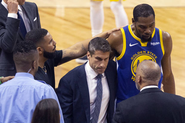 low priced a5582 32a1c Golden State Warriors forward Kevin Durant, right, is consoled by Drake as  he walks