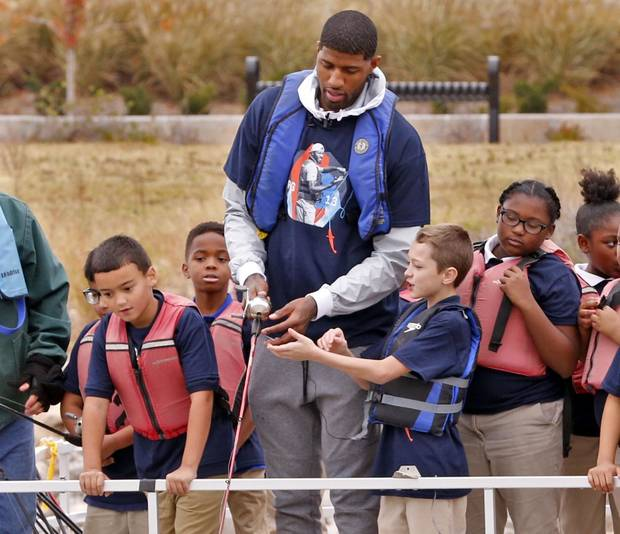 Paul George helped teach fourth-grade students how to cast a line at Monday's launch of his outdoor initiative for kids. [PHOTO BY STEVE SISNEY, THE OKLAHOMAN]