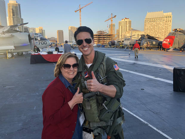 Trish the Dish poses with a Tom Cruise impersonatort on the flight deck of the USS Midway. (Photo by Berry Tramel)