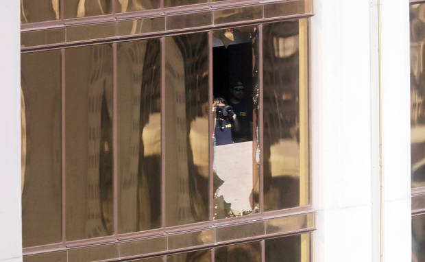 In this Oct. 4 file photo, investigators work in the room at the Mandalay Bay Resort and Casino in Las Vegas, from which shooter Stephen Paddock carried out his murderous rampage on Oct. 1. (AP Photo/Gregory Bull)