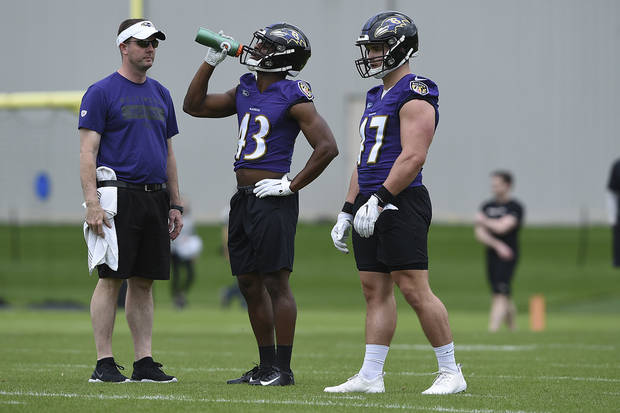 Baltimore Ravens rookie running back Justice Hill, center, drinks water during NFL Football rookie camp, Saturday, May 4, 2019 in Owings Mills, Md.(AP Photo/Gail Burton)