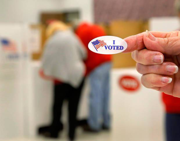 "Election Board staff member Reba Basinger holds up an ""I VOTED"" sticker Thursday at the Oklahoma County Election Board during the first day of early voting. [Photo by Jim Beckel, The Oklahoman]"