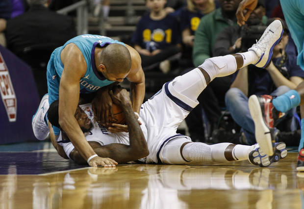 Charlotte Hornets forward Nicolas Batum (5), left, battles Memphis Grizzlies forward JaMychal Green for a loose ball in the first half of an NBA basketball game in Charlotte, N.C., Friday, Feb. 1, 2019. (AP Photo/Nell Redmond)