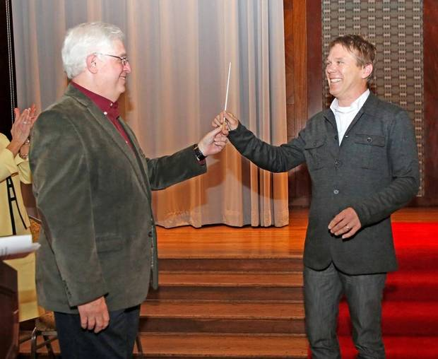 Oklahoma City Philharmonic music director Joel Levine, left, passes the conductor's baton to Alexander Mickelthwate, the philharmonic's music director designate during a ceremony Monday at the Civic Center Hall of Mirrors. Photo By Steve Gooch, The Oklahoman
