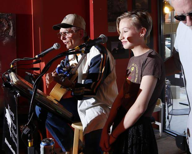 Bob Deupree enlists the help of fellow performer Ken Pomeroy as he performs during the 2016 Norman Music Festival in Norman. Pomeroy, now 15, is playing her own set this year at the Woody Guthrie Folk Festival in Okemah. [Photo by Steve Sisney, The Oklahoman Archives]