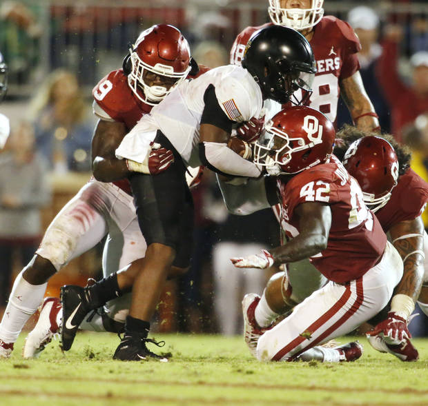 Oklahoma's Kenneth Murray, left, and Mark Jackson Jr. bring down Army's Kelvin Hopkins during Saturday's game in Norman. [PHOTO BY STEVE SISNEY, The Oklahoman]