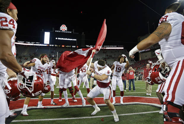 Baker Mayfield (6) plants the Sooner flag in the Ohio State logo at midfield after beating the Buckeyes 31-16 at Ohio Stadium on Saturday night. [PHOTO BY KYLE ROBERTSON, THE COLUMBUS DISPATCH]