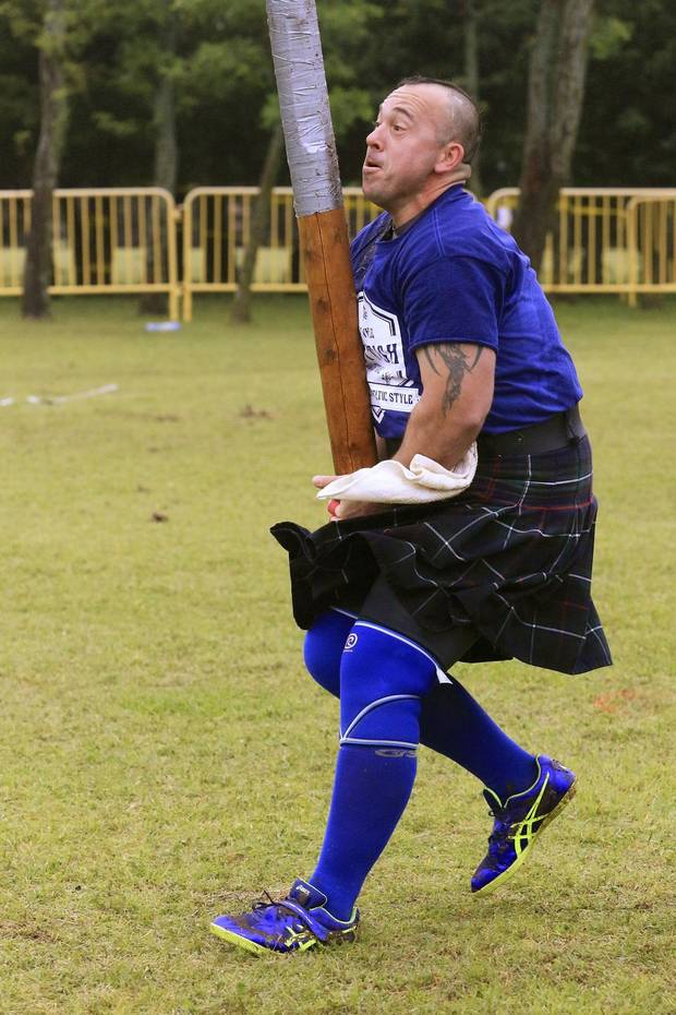 Marcelo Derousseau, from Kerrville, Texas, runs forward to toss the caber during the Iron Thistle Scottish Festival in Yukon, Okla. Saturday, April 29, 2017. [The Oklahoman Archives]