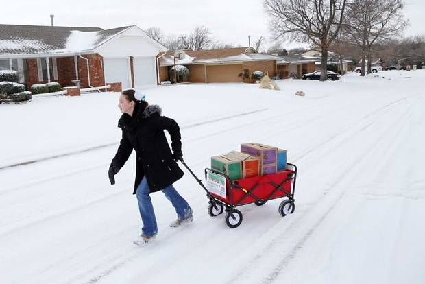 Girl Scout Katie Francis pulls her wagon full of boxes of cookies in 2014 in the snow through a neighborhood in Warr Acres selling cookies. Katie broke the record for the most Girl Scout cookies sold in a single season in 2014 and now has broken the record for the most cookies sold in the course of a Girl Scout's career. Photo by Doug Hoke, The Oklahoman Archives]