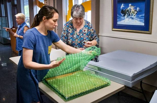 Paula Cagigal and Virginia Treadway, from left, work to pack artwork at the Red Earth Art Center in Oklahoma City, Okla. on Thursday, May 16, 2019. The center is relocating to ground floor of BancFirst Tower. [Chris Landsberger/The Oklahoman]