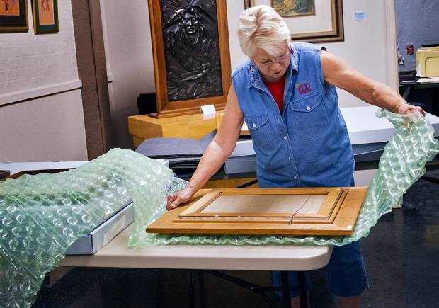 Teri Stanek works to pack artwork at the Red Earth Art Center in Oklahoma City, Okla. on Thursday, May 16, 2019. The center is relocating to ground floor of BancFirst Tower. [Chris Landsberger/The Oklahoman]