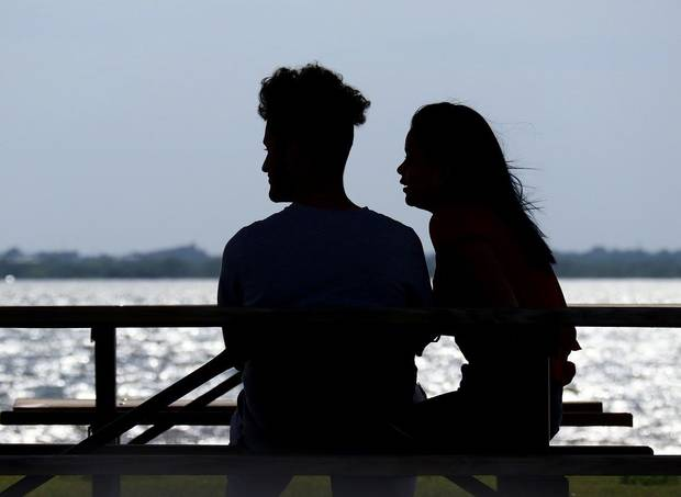 A couple sit in the shade at a picnic table and watch sail surfers enjoy the windy conditions at Lake Hefner Monday, April 27, 2020. [Doug Hoke/The Oklahoman]