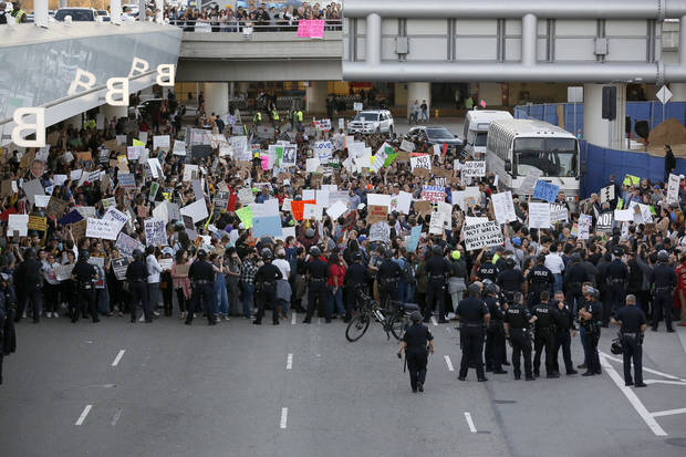 Police officers block demonstrators from marching  on Sunday on the lower roadway during a protest against President Donald Trump's executive order banning travel from seven Muslim-majority countries, at Los Angeles International Airport. (AP Photo/Ryan Kang)