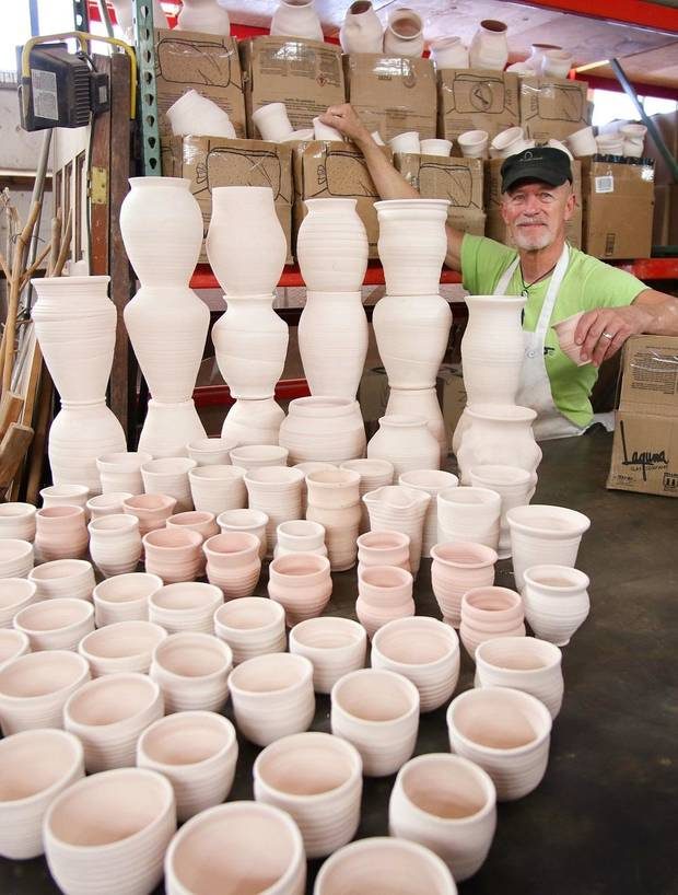 Collin Rosebrook, owner of Paseo Pottery, poses with pots made for the Pottery Place booth at the Festival of the Arts, which are now being stored because of the cancellation of the festival due to the COVID-19 pandemic, Monday, April 20, 2020. [Doug Hoke/The Oklahoman]