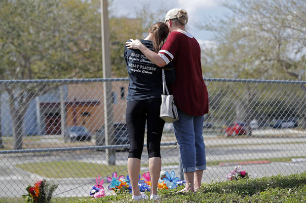 Hadley Sorensen, 16, a student at Marjory Stoneman Douglas High School, is comforted by her mother Stacy Sorensen at a makeshift memorial outside the school in Parkland, Fla., Sunday, Feb. 18, 2018, where 17 people were killed in a mass shooting on Wednesday. Nikolas Cruz, a former student, was charged with 17 counts of premeditated murder. (AP Photo/Gerald Herbert)