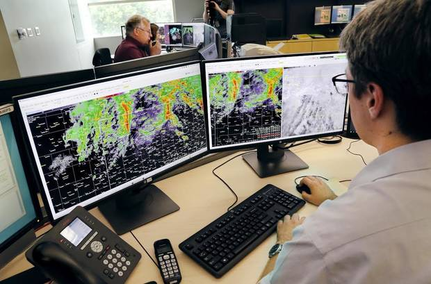 Meteorologist Alex Zwink sits at his desk studying weather models and storm patterns Monday in a room filled with fellow meteorologists and researchers with the National Weather Service Forecast Office. [Jim Beckel/The Oklahoman]