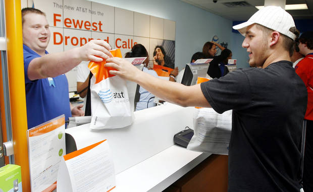 Retail sale consultant Ed Brookshire, left, hands Mike Balliet a sack with his iPhone and accessories as the iPhone first went on sale in the AT&T store at 6959 NW Expressway in Oklahoma City, Friday, June 29, 2007. Balliet was the first person to buy an iPhone at this store. [THE OKLAHOMAN ARCHIVES]