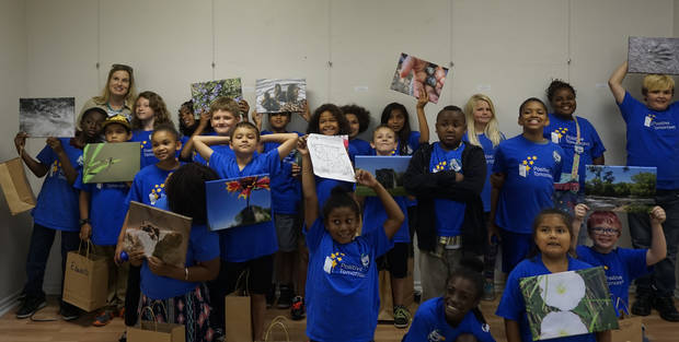 The third, fourth and fifth graders of Positive Tomorrows received nature photos they took throughout the school year at a reception on Tuesday.